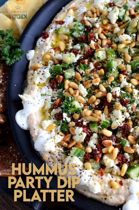 What's a party without dip? Hummus Party Dip Platter is a large, layered dip that's just perfect for entertaining a crowd. This all in one dip has hummus, sour cream, pine nuts, sun dried tomatoes, cucumbers, feta, and a few other ingredients too! #hummus #dip #partydip #partyfood #layereddip #hummusplatter #platter