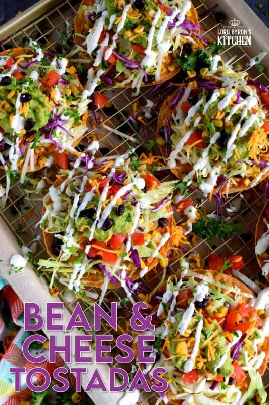 Bean and Cheese Tostadas are piled high with fresh veggies and topped with guacamole and sour cream. They're like an unrolled burrito with the crunch of a taco. Try eating just one! #tostadas #Mexican #recipes #vegetarian