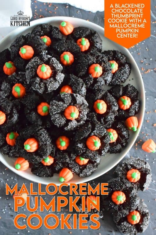 These festive cookies are deliciously decadent. The base is a chocolate cookie that has been darkened to resemble the blackness that goes hand in hand with Halloween. Before baking, the cookie is rolled in black sanding sugar which adds a glistening effect. Finally, a Mellocreme Pumpkin is pushed into the center to make these one of the most adorable Halloween cookies! #halloween #mellocreme #pumpkin #cookies #candy #candycorn
